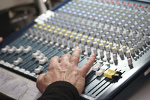 man's hand on a soundboard