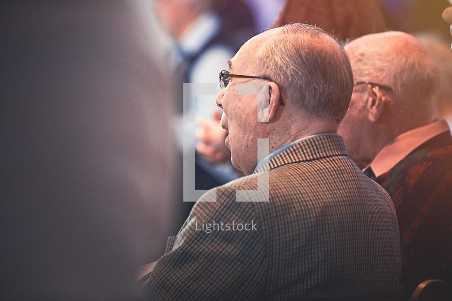 elderly men sitting in church pews at a worship service