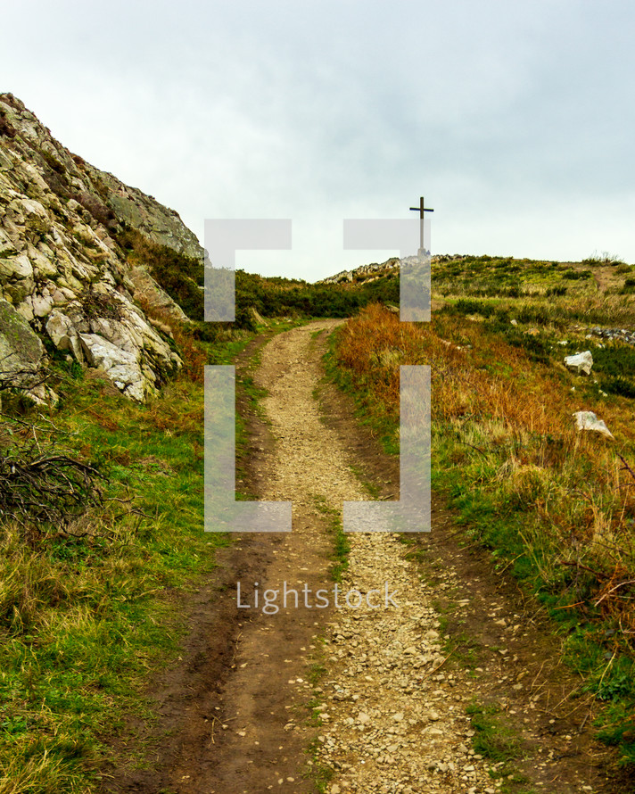 A rocky path leading toward the cross located high atop Bray Head in County Wicklow, Ireland