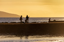 A family walking on a Salthill, Galway, Ireland jetty at sunset appear in silhouette against a yellow sky at sunset