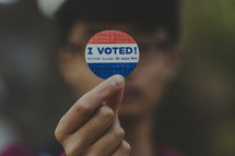 man holding up an I voted sticker