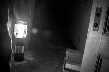 man carrying a glowing lantern into a dark abandoned room