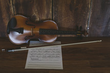 a violin, bow, and sheet music