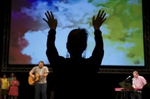 a woman with raised hands and worship leaders leading a congregation in song