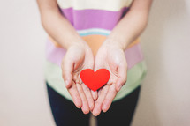 cupped hands holding a paper heart