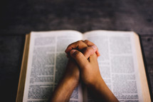 praying hands over an open Bible