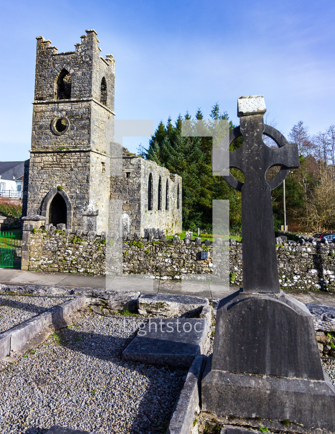Gravestone in the shape of a Celtic cross with Saint Mary of the Rosary Catholic church in the background near Cong, County Mayo, Ireland