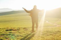 man with a guitar standing outdoors under intense sunlight