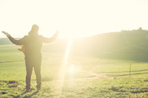 man with raised hands standing outdoors under intense sunlight