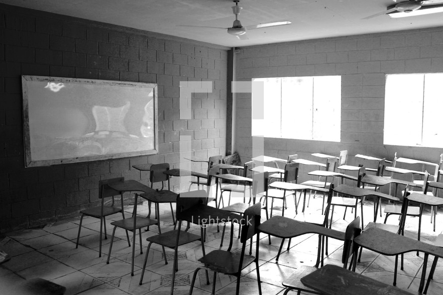 rows of student desks in an empty classroom