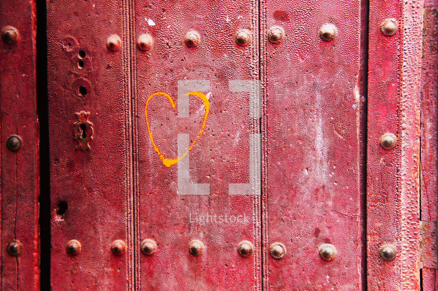 a yellow color heart painted onto a an old red door