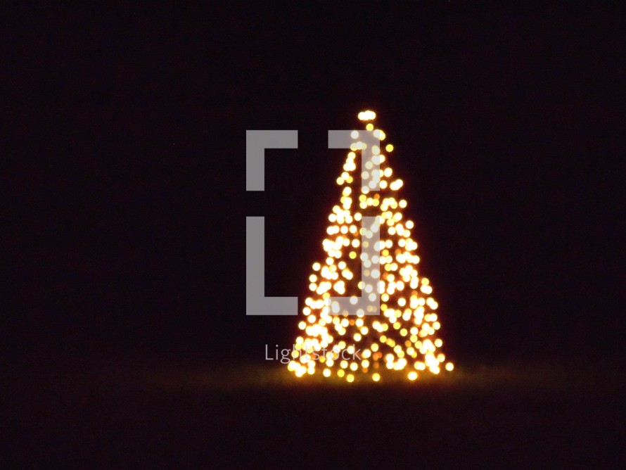 A festive Christmas tree covered in white lights brings a warm glow to the cool nights as people celebrate the glory of Christmas.