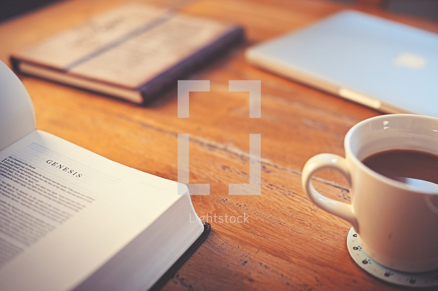 Bible opened to Genesis on a desk, coffee mug, and journal