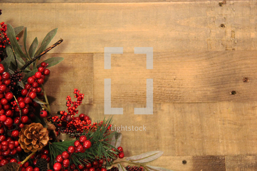 Red berries and greenery on a Christmas wreath over a wooden background