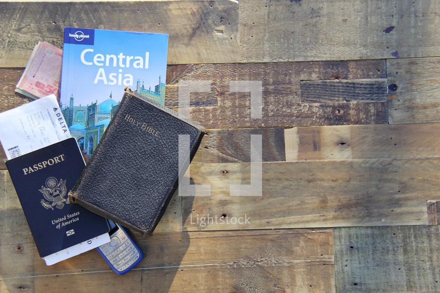 mission trip, Holy Bible, passport, map, book on Central Asia, money, boarding passes, and cellphone on a wood floor
