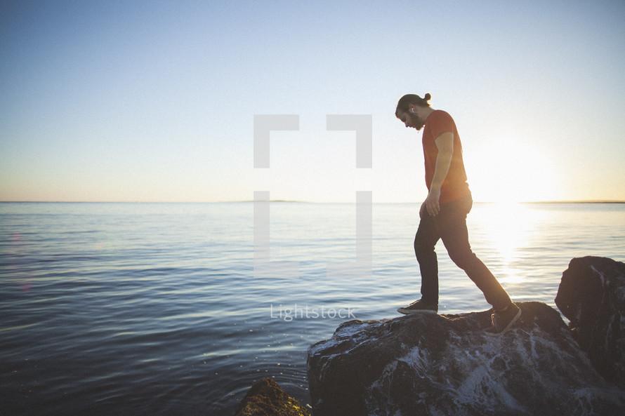 Man walking  on boulders by the ocean.