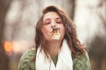 Woman blowing on a toasted marshmallow.
