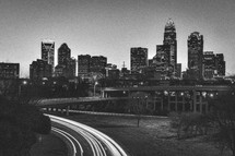 Headlights from highway traffic and a city skyline at dusk.