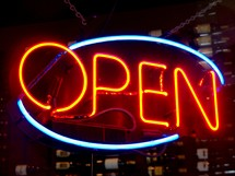 A neon yellow, read and blue open sign that tells the world it is open for business for a restaurant, business or retail establishment that lights up the night sky drawing people to the business to shop, browse and purchase items.