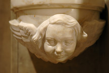 Marble face and wings of an gothic angel on a column