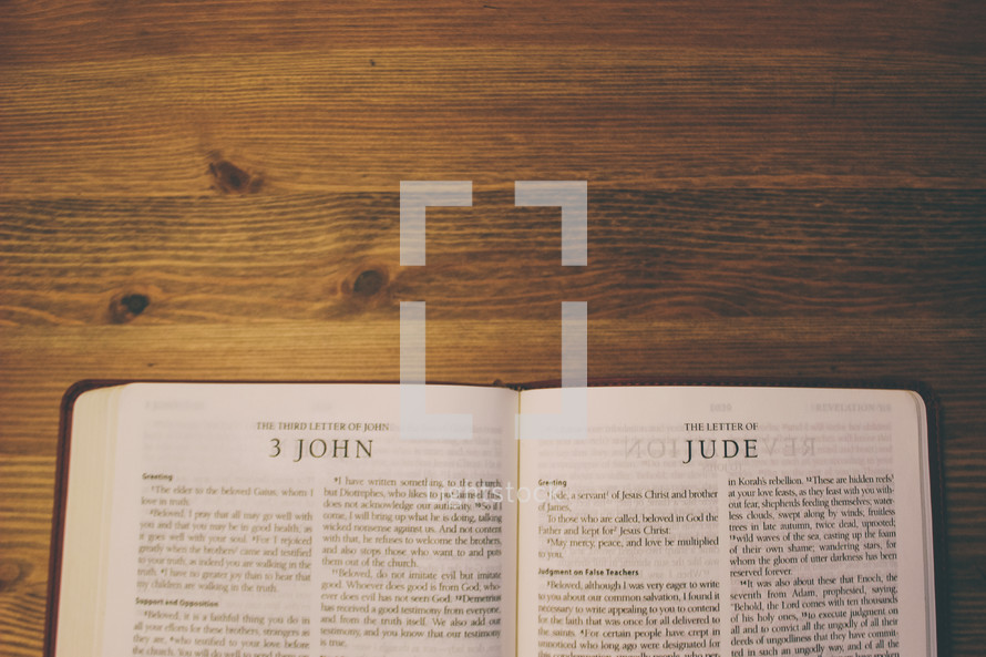 Bible on a wooden table open to the book of 3 John and the Letter of Jude.