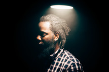 face of an African American man standing under a lamp