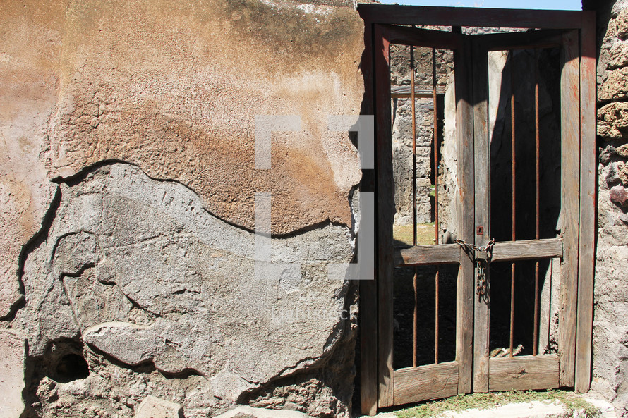Wooden gate with a chain lock on a stone building.