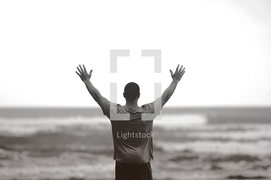 man standing in front of the ocean with raised hands