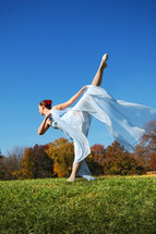Woman dancer, dancing in a field with trees with autumn foliage in the background