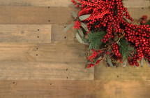 Red berries on a Christmas wreath against a wooden background