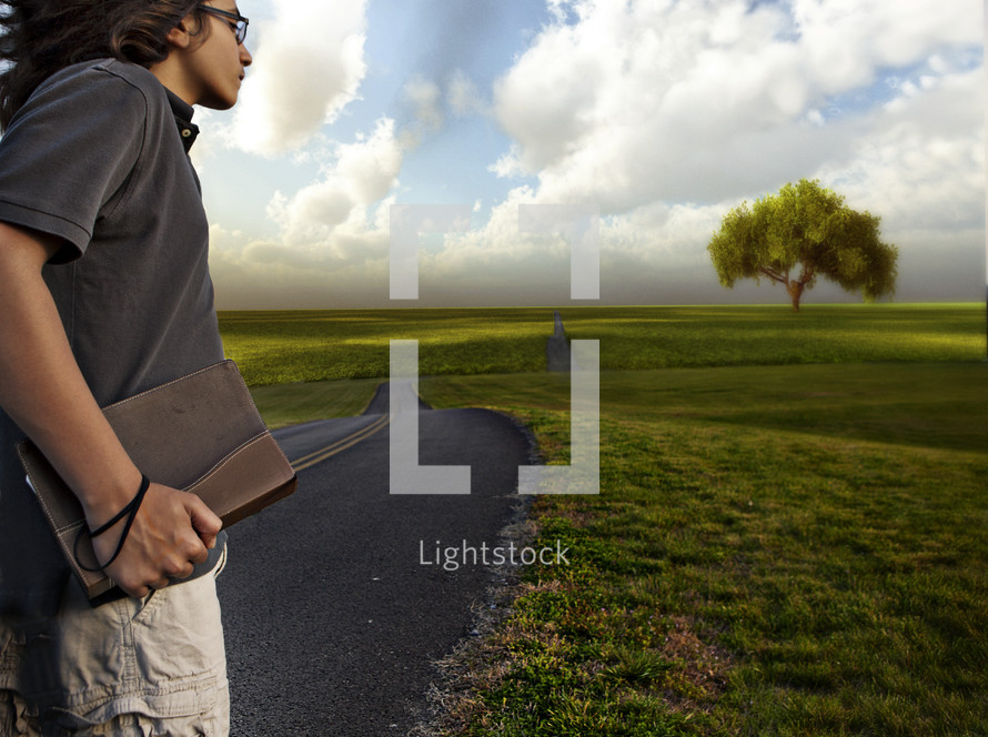teen boy holding a bible heading down the open road