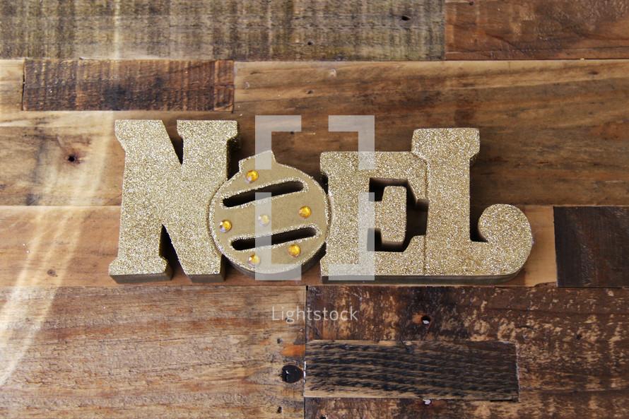Word Noel in gold on a wooden floor type background