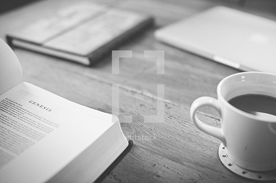 Bible opened to Genesis, coffee mug, journal