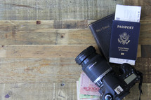 travel, camera, passport, map, book on Central Asia, money, boarding passes, wood floor