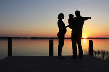 Silhouette of a family on a pier by the water at sunset.