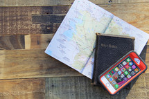 map, Holy Bible, and cellphone on a wood floor
