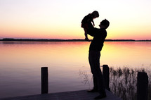 silhouette of a father holding up his son in front of a lake