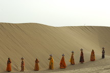 female Hindu women walking with water jugs on their heads