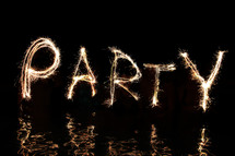 The word 'Party' written in firework sparklers  (by five 'artists' standing in waist high water).
