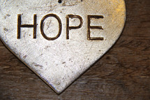 The word hope on a silver ornament with wooden background