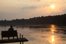 man sitting on a dock at sunset