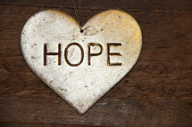 hope on a silver ornament  against a wooden background