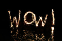 """Wow"" written in fireworks by  four 'artists' standing up the their waists in water."