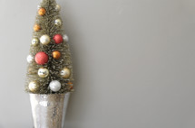 small decorated Christmas tree against a white/grey background