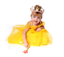 young girl dressed in a yellow princess dress, wearing a crown, carrying a wand