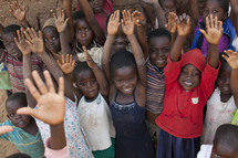 Children in Malawi, Africa with hands raised.