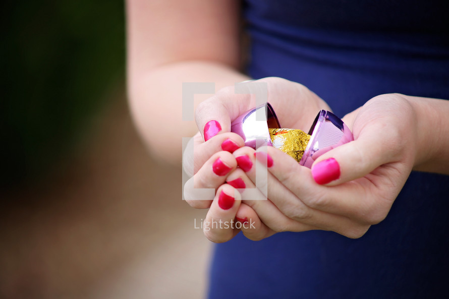 a plastic Easter egg in a woman's cupped hands
