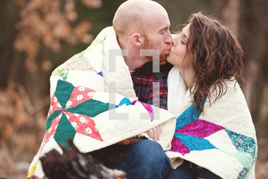 Couple wrapped in a quilt kissing.