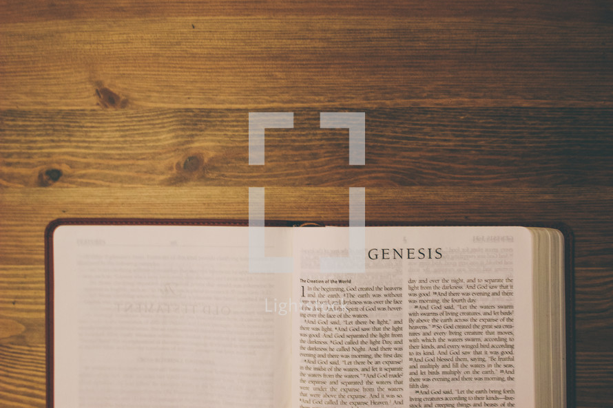 Bible on a wooden table open to the book of Genesis.