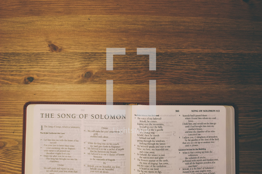 Bible on a wooden table open to the book of the Song of Solomon.